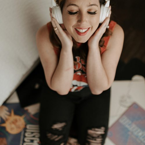 girl wearing headphones on pile of records talking about burnout
