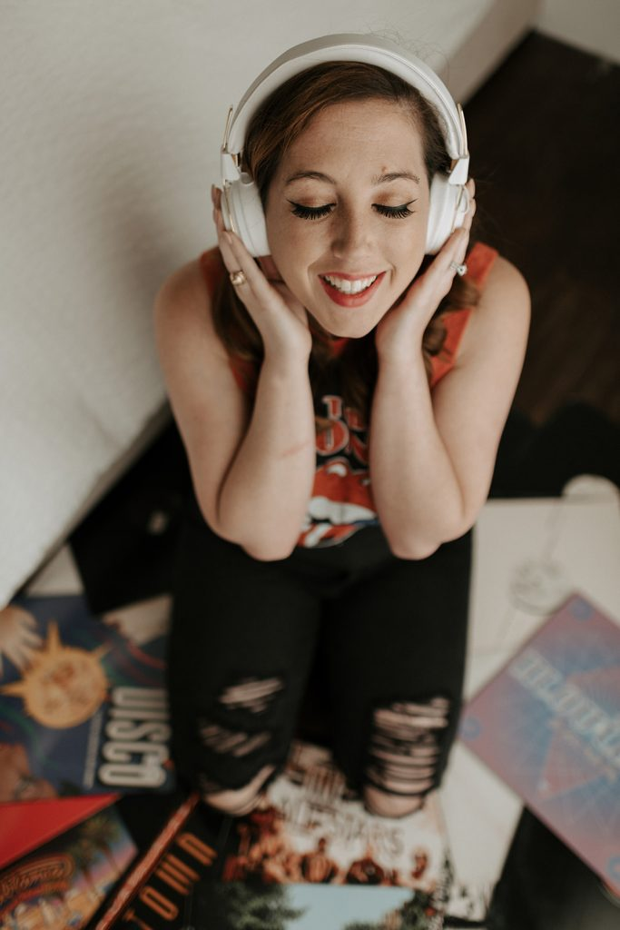 girl in picture holding headphones on pile of records worried about burnout